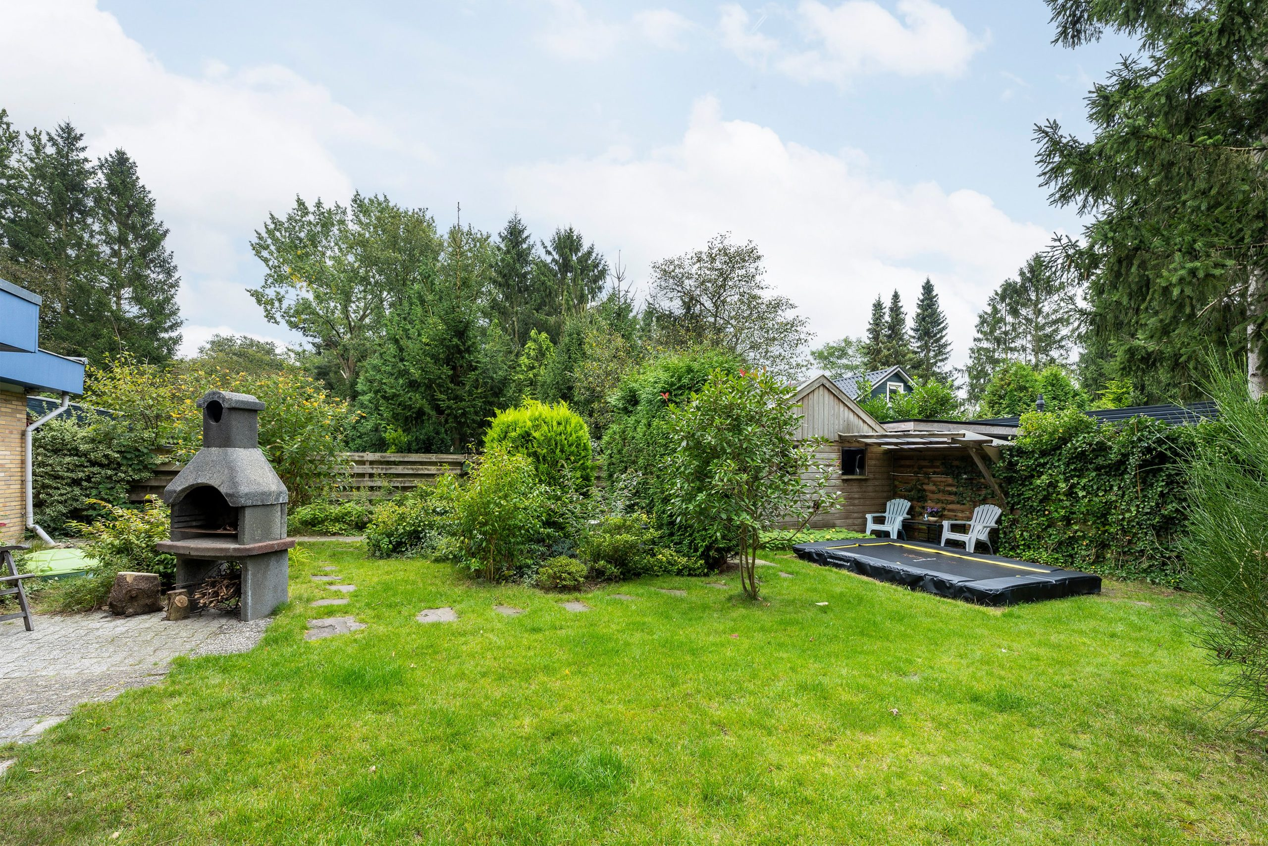 blauwe-boshuis-tuin-met-trampoline-en-haard